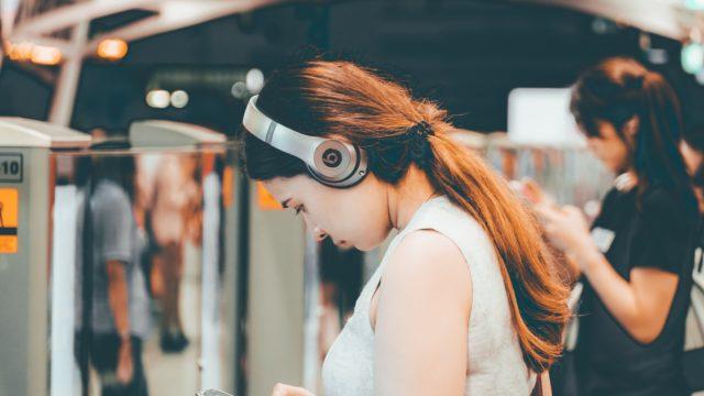 通勤電車でウォークマンで聴いている女性の写真
